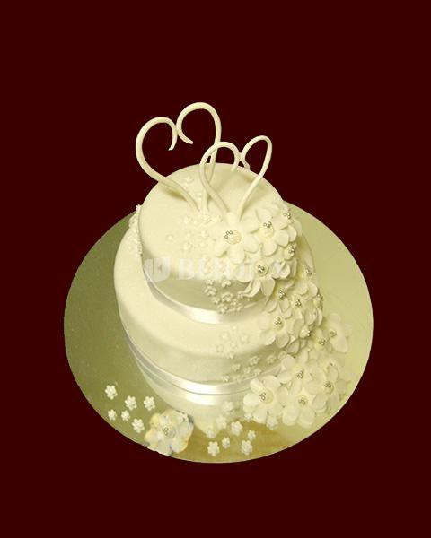 Dviejų aukštų tortas su baltomis gėlytėmis ir širdelėmis ant viršaus